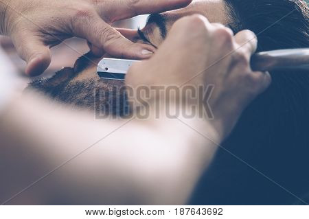 Close-up hands of barber holding razor and shaving a client.