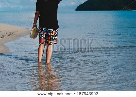 Asia Woman Wearing Black Shirt And  Holding Sandal Standing Alone In Sea . This Image For People,tra