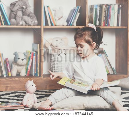 Cute emotional little girl reading book to her toy.