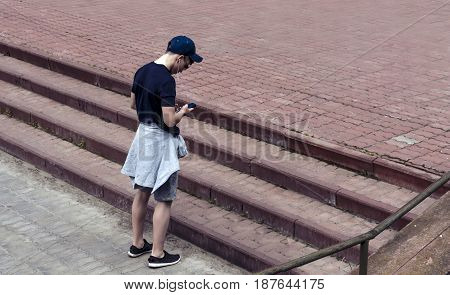young man with the phone on a city street listening to music