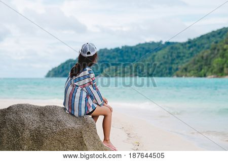 Asia Woman Wearing Sunglasses Sitting On Rock And Admire Scenery View Front Of Her. Have Blue Sea An