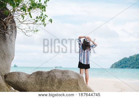 Asia Woman Standing On Sand Beach And Putting Hand On Head Herself. Have Big Rock Placed Behind And