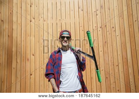 Man in glasses with scooter in street standing by wooden wall