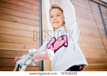 Photo of girl on cycle near wooden building