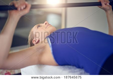 Close-up side view of young blonde woman in blue top doing bench pressing exercise with bar-bell in gym