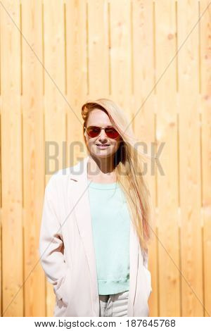 Young woman near wooden wall in street during day