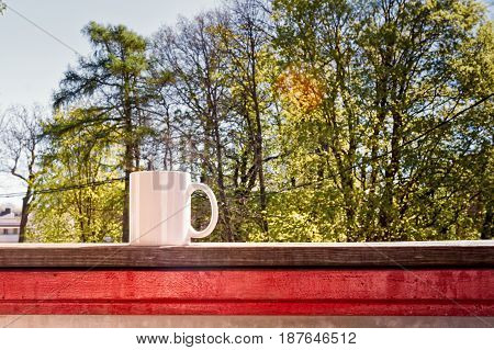 A white cup of tea on a rail of a balcony on a beautiful spring morning.