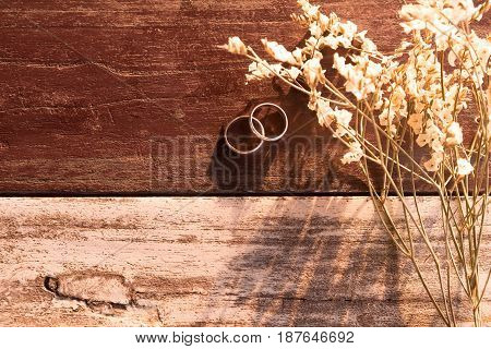Top View And Warm Tone. Two Silver Ring Put Beside White Bouquet Flower All Of This Putting On Woode
