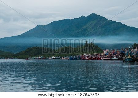 Beautiful Blue Sea, Fisherman Village On Coast And Have Big Mountain, Fog Are Bacgkround. This Image