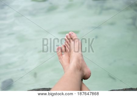 Young Woman Legs Sitting On Beach And Cross Leg With Water Are Background. This Image For People,nat