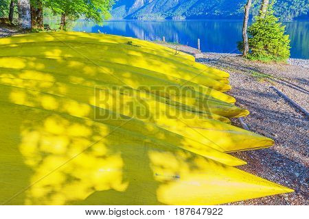 Yellow canoes in a row on the beach of a Bohinj lake Slovenia