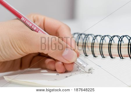 pencil eraser, pencil eraser removing a written mistake on a piece of paper, delete, correct, and mistake concept.