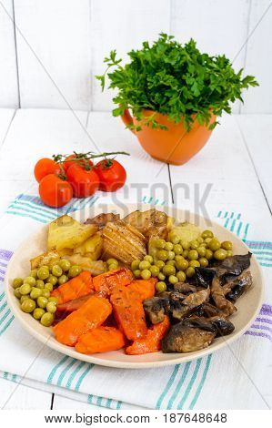 Vegetarian breakfast: baked vegetables (potatoes carrots) mushrooms green peas on a plate on a white wooden background. Healthy food.