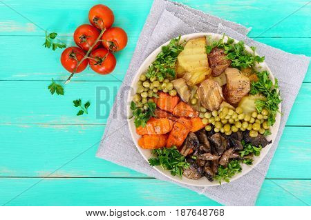 Vegetarian breakfast: baked vegetables (potatoes carrots) mushrooms green peas on a plate on a light wooden background. Healthy food. The top view