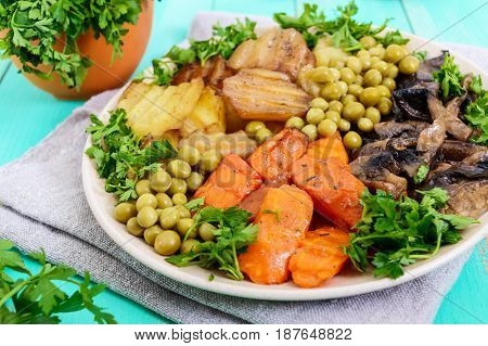Vegetarian breakfast: baked vegetables (potatoes carrots) mushrooms green peas on a plate on a light wooden background. Healthy food. Close up