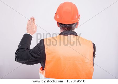 Back View Of Engineer Wearing Hardhat Making Oath Gesture