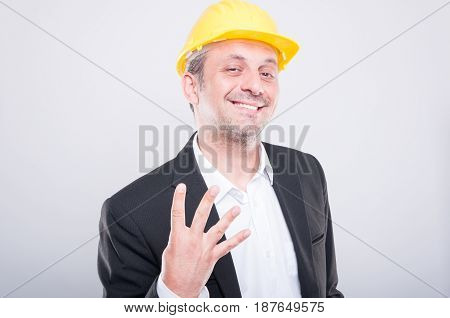Portrait Of Attractive Contractor Showing Number Four Gesture