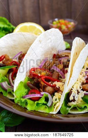 Tacos is a traditional Mexican dish. Tortilla stuffed with chicken bell and hot peppers beans lettuce cheese blue onion with salsa sauce on dark wooden background. Vertical view