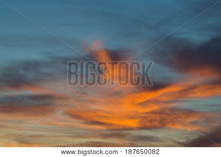 natural sunset in dramatic blue sky with clouds in orange color tones