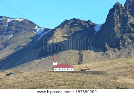 Red roof and steeple on the chapel in the village of Vik.