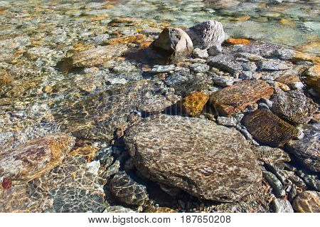 crystal clear water and colorful stones of natural wild swiss river verzasca
