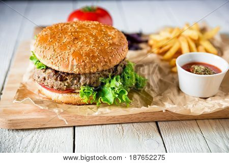 Classic american hamburger with beef and french fries on white table