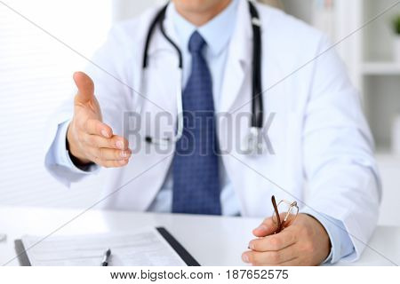 Male medicine doctor offering helping hand for handshake. Partnership and trust concept