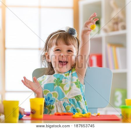 Smiling child girl is learning to use colorful play dough in a well lit room near window