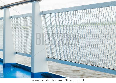 Detail view of metal grid on shipt banister with blurred sea on background