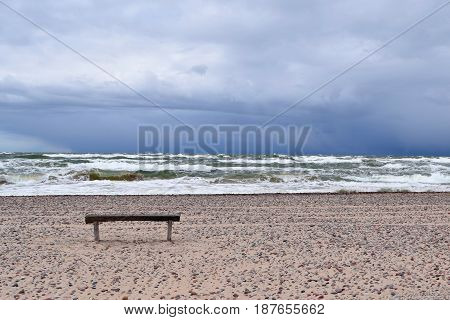 Lone bench beach. Approaching rain, large, white waves of the sea. Latvia.