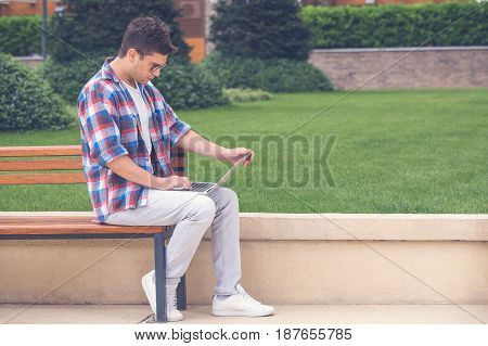 Handsome fashionable guy sitting on bench in the park with his hands on computer keyboard and looking at laptop screen. Freelancer concept.