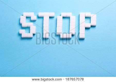 The word stop from cubes of sugar. Sugar kills. Blue background with an empty space for the text paste copy.