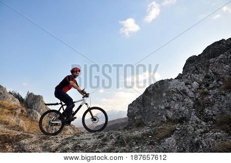 Young man riding a bike on hill under a mountain, extreme riding bicycle off road on rocks