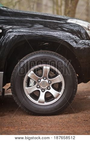 Close-up photo wheel of an SUV that stands in the woods.