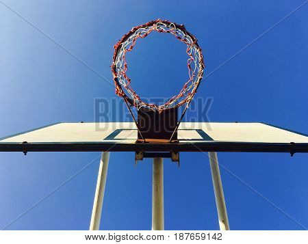 Basketball Hoop or Sportive Basket with Ring Equipment of Sport Gym Againt with Blue Sky. Looking Up View from Below.