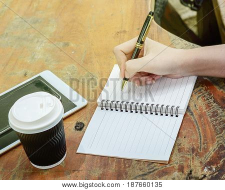 Woman hand is writing on notebook under sun light on wooden table