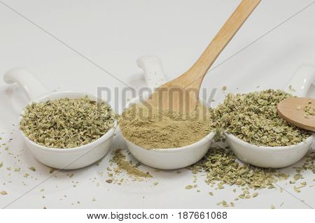 Three spoons with oregano, in the center Oregano milled, the others contain dried leaves