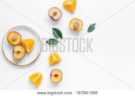 cut peach and orange for exotic fruit on plates on white table background top view mockup