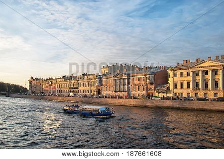 SAINT - PETERSBURG, RUSSIA - MAY 18, 2017: Excursion boats with tourists sail along  residential houses on the embankment of The Fontanka River in spring sunny evening