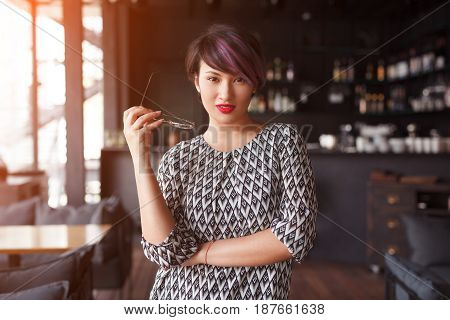 Young woman with red lips wearing dress and posing confidently on background of cafe.