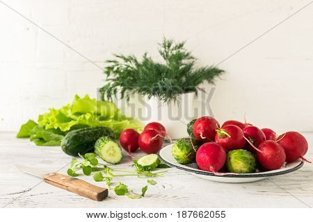 Fresh vegetables young radishes and cucumber for preparing a light salad on the kitchen table. Light wooden background. Selective focus