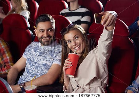 Positive girlfriend drinking cola and taking self portrait at smart phone with her stylish arabian boyfriend in cinema. Happy couple making photo at call phone, having fun, posing, when watching movie.