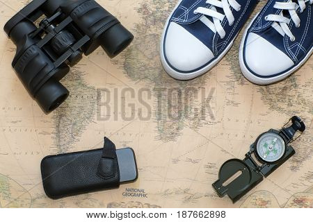 Items needed for the journey: a compass binoculars telephone sneakers. Located on a world map background.