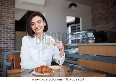 Young businesswoman holding cup of coffee while sitting in cafe with smartphone and looking at camera.