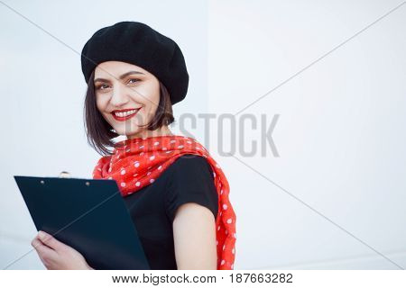 Beautiful adult woman in elegant clothing posing with file in hands and looking at camera.