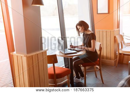 Elegant adult woman sitting at table in cafe and working with laptop.
