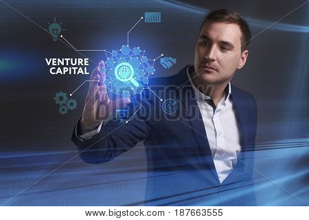 Business Technology Internet and network concept. Young businessman working on a virtual screen of the future and sees the inscription: Venture capital