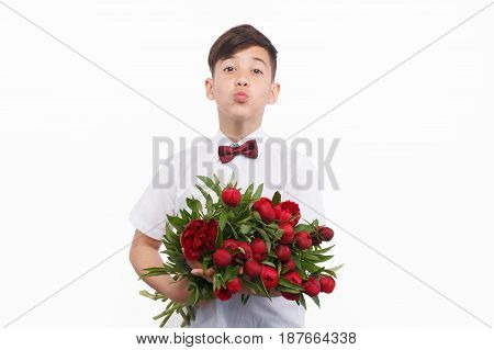 Young male teen holding an bunch of flowers and giving air kiss to camera isolated on white.