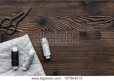 sewing hobby with tools, thread, scissors wooden desk background top view space for text