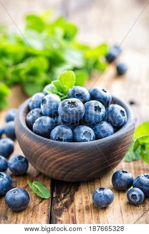 Fresh blueberry in bowl on wooden table closup